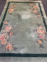 GREEN GROUND CHINESE WASHED WOOLLEN RUG, G H Ffrith Ltd with corner floral sprays, single band