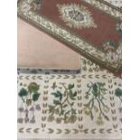 MODERN WOOLLEN RUGS (3) - a cream ground example with repeating block floral pattern and tasselled