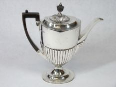 A SILVER COFFEE POT - of oval form with half reeded body to a shallow pedestal, handle and knop