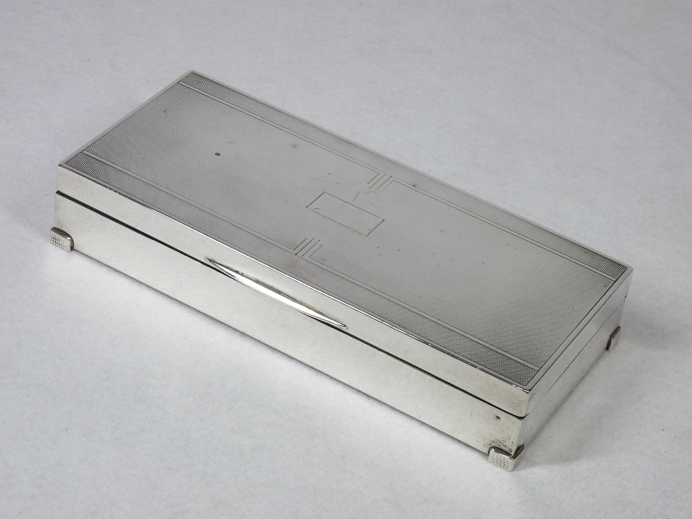 AN OBLONG ENGINE TURNED SILVER MOUNTED CIGARETTE BOX with two interior compartments and on neat