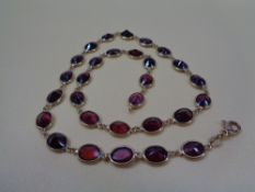 ITALIAN 18CT GOLD & GARNET NECKLACE of 29 facet cut stones, oval mounted with looped ends, 44cms