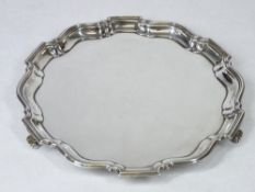 A SMALL SILVER CIRCULAR LETTER TRAY - uninscribed with wavy border on three scroll supports,
