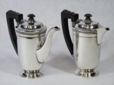 A PAIR OF SILVER COFFEE POTS - plain bodies on a pedestal base with stepped top, handles and knops