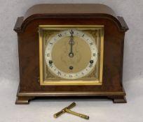ELLIOTT OF LONDON WALNUT CASED MANTEL CLOCK - having winged mask spandrels and silvered chapter ring