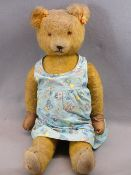 MID-CENTURY MOHAIR TEDDY BEAR - in a child's colourful Boots chemist's dress, the Teddy quite