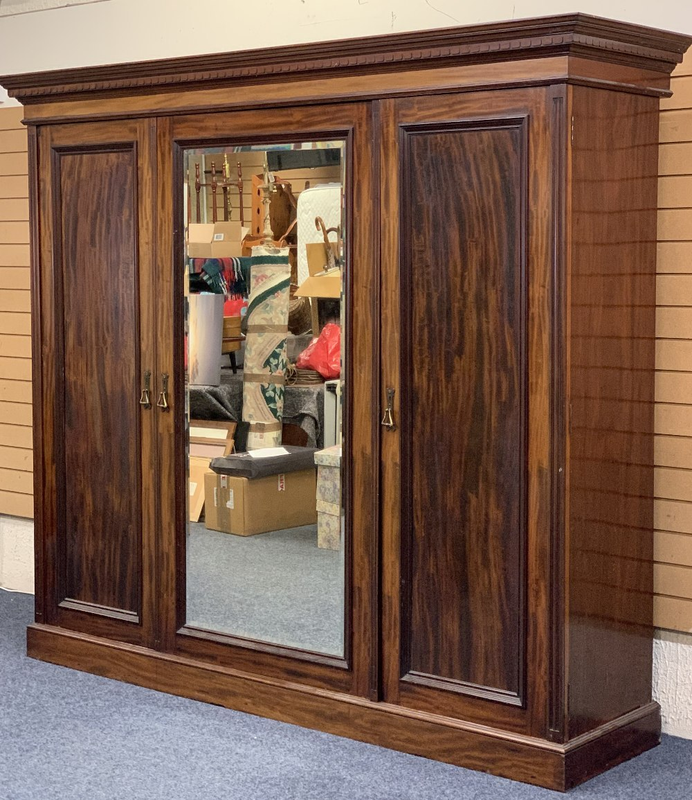 CIRCA 1900 MAHOGANY TRIPLE WARDROBE with dentil carved cornice and large central mirrored door