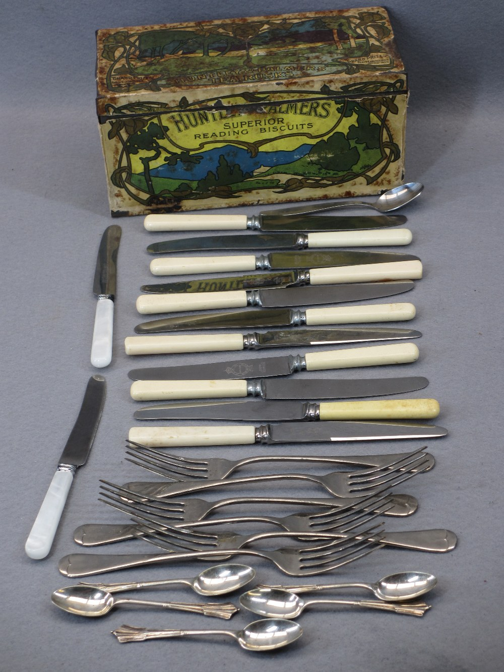 EP & OTHER CUTLERY - in a rare paper covered Huntley & Palmer's Tea Rusks tin, Art Nouveau style