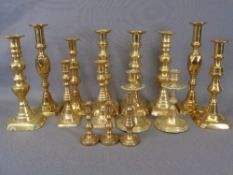 BRASS CANDLESTICKS - seven pairs and one odd, graduated from 27.5cms the tallest