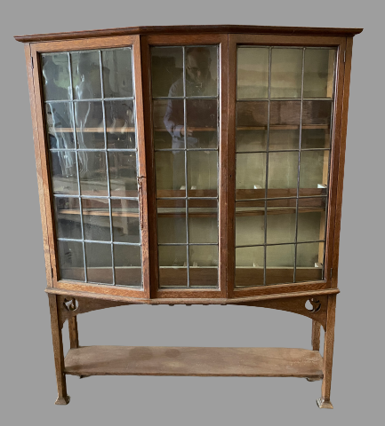 ARTS & CRAFTS STYLE BOOKCASE CUPBOARD with angular bow front and leaded glass doors, 147cms H,