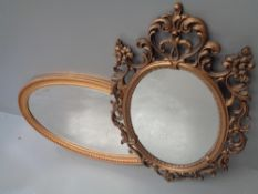 MIRRORS (two) - a gilt framed oval with bevelled glass, 57 x 93cms and an ornate mirror