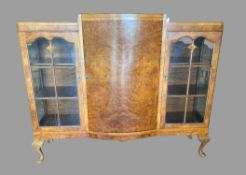 BURR WALNUT BOOKCASE - Queen Anne style with two glazed doors either side of a bow front, on