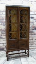 EARLY 20TH CENTURY CARVED OAK & LEADED GLASS BOOKCASE with applied mouldings, turned cup and cover