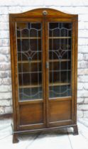 EARLY 20TH CENTURY STAINED OAK & LEADED GLASS BOOKCASE, arched top and scrolled bracket feet, 183cms