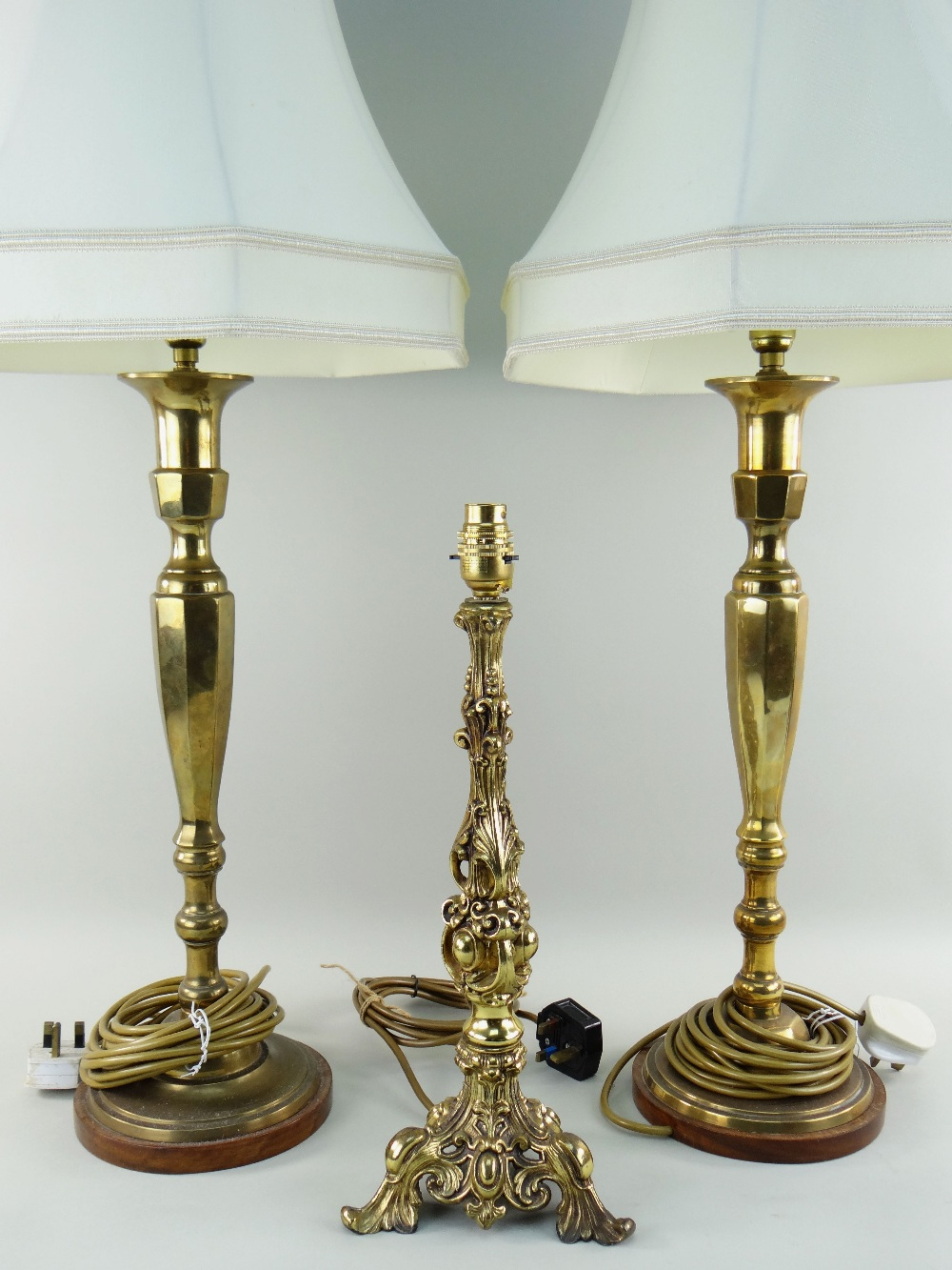 PAIR OF CONTINENTAL BRASS TABLE LAMPS on wooden bases with ivory cloth shades, sticks 40cms high and