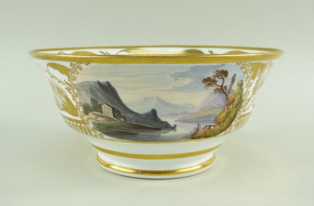 A SWANSEA PORCELAIN LANDSCAPE DECORATED TEA BOWL of footed form with flared body, London decorated