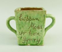 A EWENNY SLIPWARE POTTERY TWIN HANDLED MEAD CUP square based, mottled lime green glaze, with