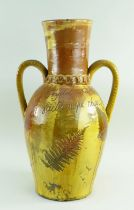 A 19TH CENTURY SLIPWARE POTTERY TWIN HANDLED VASE with elongated neck and two loop handles, clear