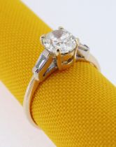 18CT GOLD DIAMOND RING, the central stone (0.7cts approx.) flanked by diamond tapering baguette