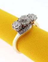 18CT GOLD THREE STONE DIAMOND RING, the three primary stones (totalling 1.0cts approximately) on a