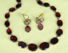GARNET SET RIVIERE NECKLACE, the thirty graduated oval-shaped stones closed set in yellow metal,