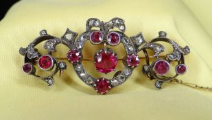 YELLOW & WHITE METAL SET DIAMOND & RUBY BAR BROOCH of naturalistic bow, scroll and leaf design, 11.