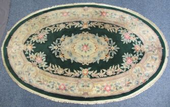OVAL CHINESE WASHED WOOLLEN RUG - green ground with bold floral design and tasselled edging, 260 x