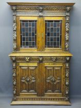 CONTINENTAL STYLE CARVED OAK BOOKCASE SIDEBOARD - with leaded coloured glass upper doors, lion mask,