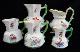 FIVE SWANSEA POTTERY JUGS including graduated trio, all with green twig-handles, enamelled flowers