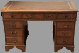 REPRODUCTION MAHOGANY PEDESTAL DESK with gilt tooled leather top, three frieze drawers and twin