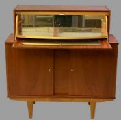 MID-CENTURY TEAK COCKTAIL CABINET with drop down top section and mirrored interior over twin opening