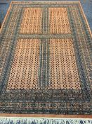 EASTERN STYLE WOOLLEN CARPET - rust ground with repeating central block and traditional patterned