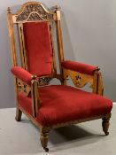 EDWARDIAN GENT'S EASY CHAIR with carved back on turned front supports with castors and red velour