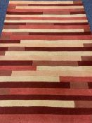 MODERN HAND LOOMED INDIAN WOOL PILE RUG having tonal reds and creams in a repeating block pattern,