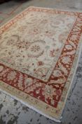 PERSIAN-STYLE IVORY & CORAL RUG, pale floral field within coral border of palmettes and serrated