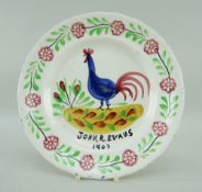A LLANELLY COCKEREL PLATE WITH DEDICATION to John R Evans, 1907 in black, the cockerel standing on a