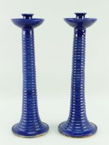 A PAIR OF EWENNY POTTERY TALL CANDLESTICKS circular based with ribbed tapering stems, bowl shaped