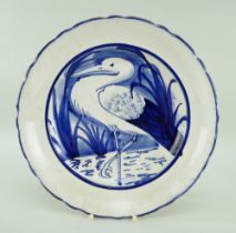 LLANELLY POTTERY PLATE with crimped rim, painted with a standing heron or stork amongst reeds,
