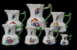 GRADUATED SET OF SEVEN DILLWYN SWANSEA POTTERY JUGS of faceted form with green enamelled twig