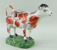 SWANSEA PEARLWARE COW CREAMER standing over a grassy rectangular base, iron-red and pink lustre