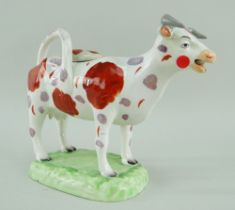 A RARE LLANELLY COW CREAMER in the familiar Swansea style with tail as loop handle and standing over