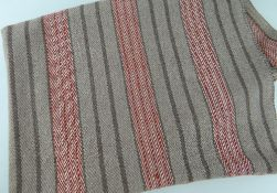 AN ANTIQUE WELSH NARROW LOOM COARSE WOOL BLANKET, in brown ground with flecked red bands and dark