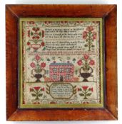 AN 1843 WELSH WOOL SAMPLER TO ELIZABETH EDWARDS, containing a series of flowers in vases around a