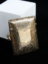 EDWARD VII 9CT GOLD VESTA CASE, of slightly curved rectangular form, scroll engraved with vacant