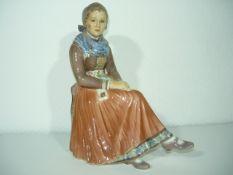 Dahl Jensen, Copenhagen. Große Porzellanfigur. Sitzende schöne Frau in Tracht. II.W. h. 22cm.