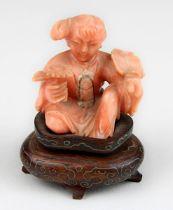 Chinesische Miniatur-Figur eines sitzenden Mädchens mit Fächer und Blume aus lachsfarbener