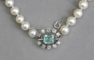 A cultured pearl necklace with an emerald and diamond brooch clasp