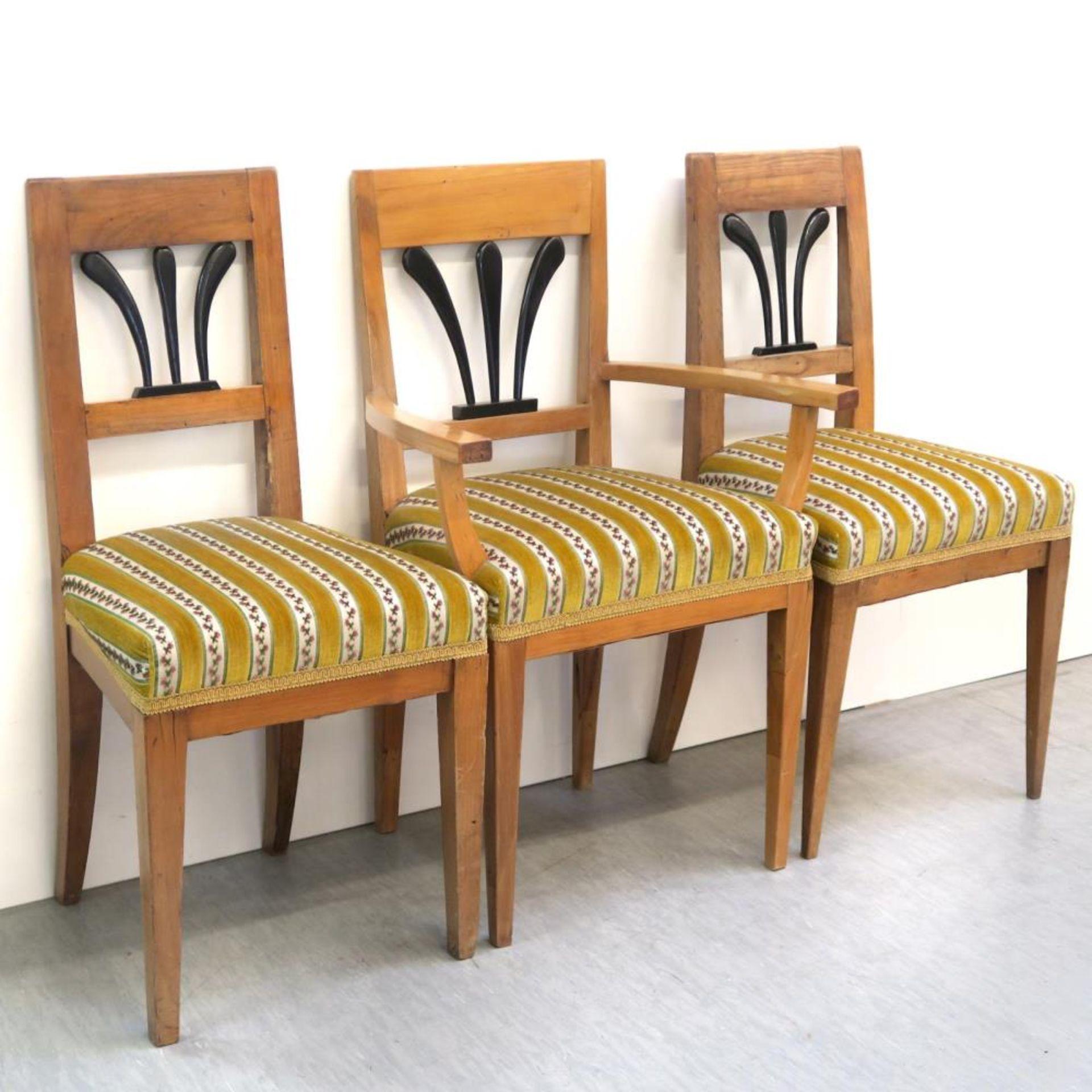 Ein Paar Stühle und ein Armlehnstuhl