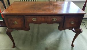 A late 19th early 20th Century Walnut Dressing Table with a three drawer front on carved cabriole