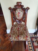 A really good 19th Century Irish Oak Hall Chair with a X frame base, gargoyle support at carved