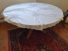 A reproduction circular Table on tripod support to seat eight people.